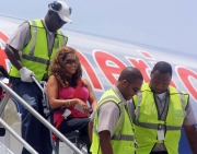 Woman-in-wheelchair-being-carried-down-airplane-stairs