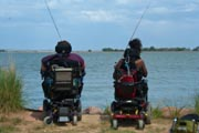 Two-people-in-wheelchairs-fishing-on-the-edge-of-lake
