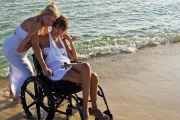 Young-woman-in-wheelchair-on-the-beach-with-her-mother