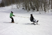 Woman-learning-to-sit-ski-with-an-instructor