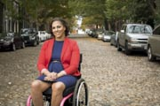 Young-woman-in-wheelchair-in-an-old-leafy-cobblestoned-city-street
