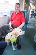 Vision-impaired-man-with-guide-dog-travelling-on-tram-together,