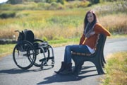 Young-woman-in-wheelchair-in-coastal-urban-park