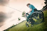 Young-man-in-wheelchair-with-young-child-by-the-lake-fishing