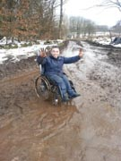 Young-man-in-wheelchair-making-hard-work-of-muddy-country-lane-in-winter