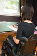 Young-female-fashion-designer-using-power-wheelchair-sketching-her-new-design