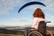 Young-woman-in-wheelchair-on-hillside-watching-paragliders