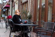 Woman-using-mobilty-scooter-sitting-at-sidewalk-cafe