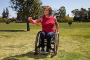 Woman-in-wheelchair-throwing-frisbee-in-park