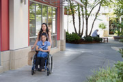 A-young-woman-using-wheelchair-out-shopping-with-friend