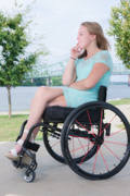 Young-woman-using-wheelchair-in-riverside-park