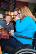 Young-mother-in-wheelchair-with-her-family-in-cafe