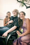 Young-man-in-wheelchair-with-two-beautiful-young-woman-for-an-afternoon-by-the-lake