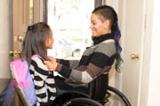 Young-mother-in-wheelchair-preparing-her-daughter-for-school