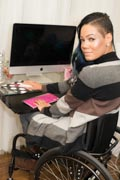 Young-professional-woman-in-wheelchair-working-on-her-computer