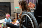 Young-mother-using-wheelchair-with-her-baby