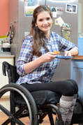 Young-woman-using-wheelchair-relaxing-with-slice-of-cake