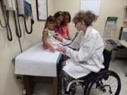 Female-doctor-in-wheelchair-treating-young-family
