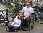 Amsterdam;couple;wheelchair;male;traveling;tourist;canal;bridge;smiling;fun;bikes